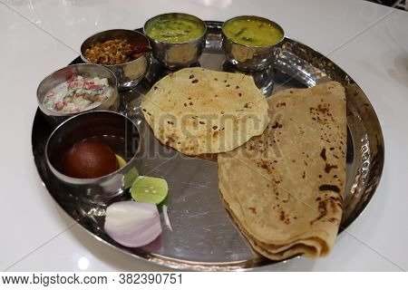 North Indian Thali Consisting Of Multiple Bowls Full Of Curries, And Dessert With Salad. Indian Food