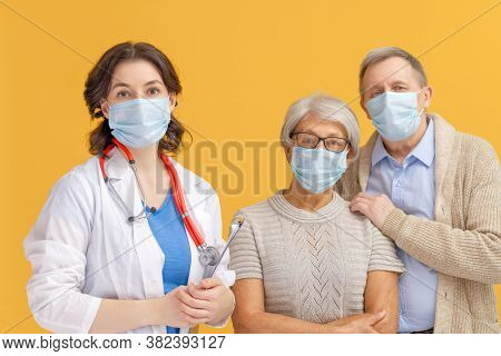 Doctor and senior couple wearing facemasks during coronavirus and flu outbreak. Virus protection, home quarantine. COVID-2019. Taking on masks. People on yellow color background.