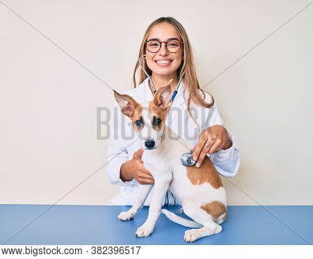 Young beautiful blonde veterinarian woman checking dog health using stethoscope smiling with a happy and cool smile on face. showing teeth.
