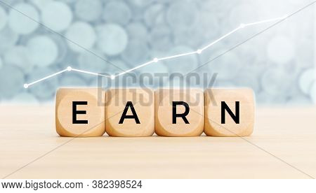 Earn Concept. Wooden Blocks With Text On Table And Chart At Background. Copy Space