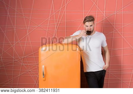 Macho Drink At Retro Fridge On Pink Background. Man Hold Cup Of Tea Or Coffee In Kitchen. Bachelor W
