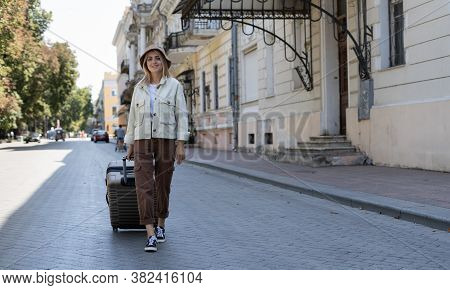 Tourist Woman Walks With A Suitcase Down The Street In A European City, Tourism In Europe. Walking T