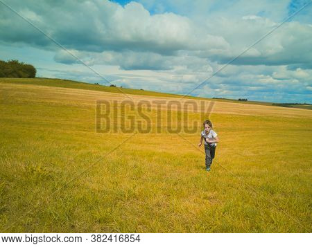 5-year-old Caucasian Boy In Light T-shirt Runs In Distance Across Yellow-green Autumn Mown Field In