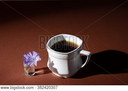 White Cup Of Instant Chicory Drink Or Coffee With Chicory Flowers On A Brown Background. Healthy Foo