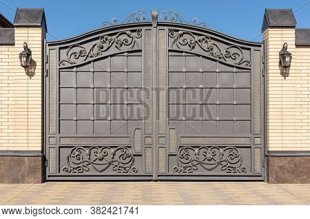Wrought Iron Gates With Ornament. Facade Of The House.