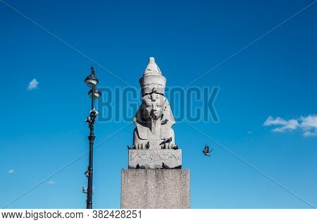 Ancient Statue Of Egyptian Sphinx With Forged Streetlight Against Blue Sky In Sunny Day