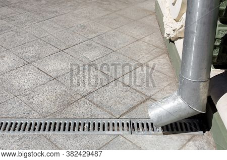 An Engineering Structure A Downspout With A Drainage Grate Against A Background Of A Gray Stone Gran