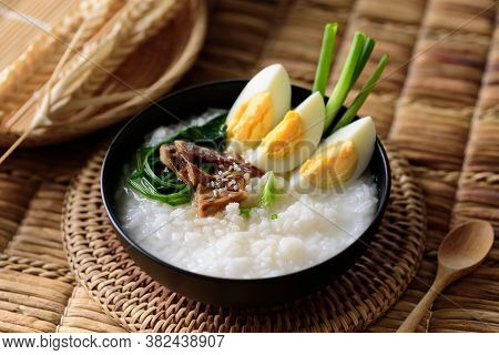 Asian Food, Rice Soup With Boiled Egg, Grilled Mushroom And Spinach In A Bowl On Woven Rattan Sheet