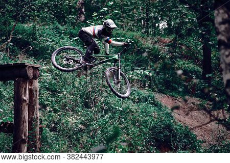 Russia, Moscow - August 26, 2020: Professional cyclist jumping with mtb over gravel. Biker riding in