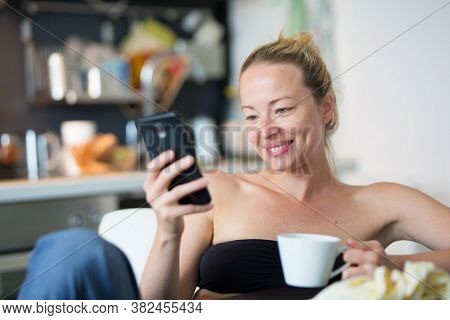 Young Smiling Cheerful Pleased Woman Indoors At Home Kitchen Using Social Media On Mobile Phone For