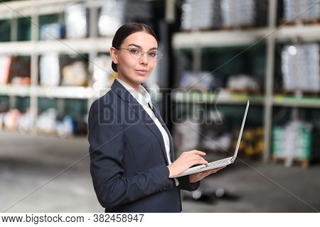 Wholesale And Logistics Concept. Manager Using Laptop In Warehouse