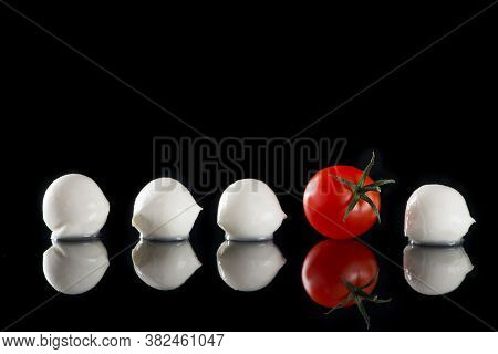 Close Up Of Mozzarella Cheese And Fresh Cherry Tomato Isolated On A Black Background With Reflection