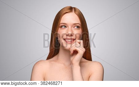 Happy Young Woman With Red Hair Smiling And Looking Away While Dreaming About Clean Skin After Spa S