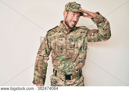 Young caucasian man wearing camouflage army uniform very happy and smiling looking far away with hand over head. searching concept.
