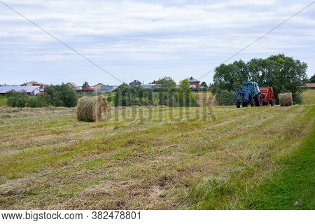 Rybushkino Village, Russia - July 1, 2020: A Blue Tractor Collects Dry Grass In Large Round Rolls Of