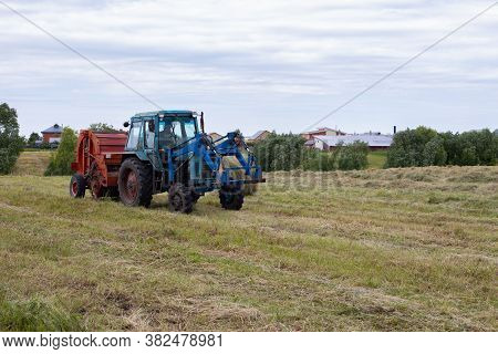 Rybushkino Village, Russia - July 1, 2020: Close-up Blue Tractor Collects Hay From Dry Clover Grass.