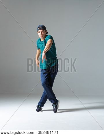 Stylish Guy Breakdancer Dancing In Studio Isolated On Gray Background. Breakdance Lessons