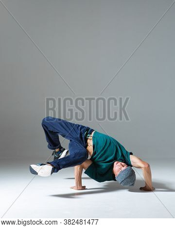 Stylish Young Guy Breakdancer Dances Hip Hop On The Floor In Studio Isolated On Gray Background. Dan
