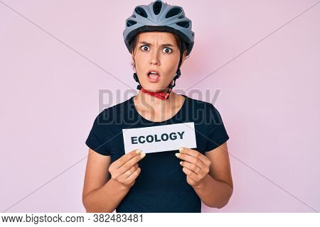 Beautiful caucasian woman wearing bike helmet holding ecology word in shock face, looking skeptical and sarcastic, surprised with open mouth