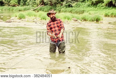 Brutal Man Wear Rubber Boots Stand In River Water. Satisfied Fisher. Fisher Masculine Hobby. Fisher