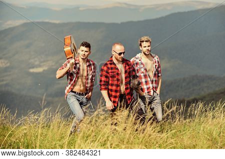 Tourists Hiking Concept. Group Of Young People In Checkered Shirts Walking Together On Top Of Mounta