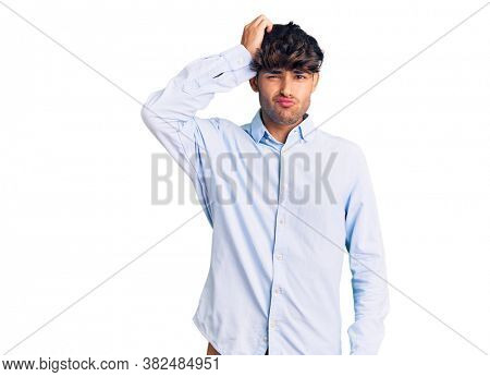 Young hispanic man wearing casual shirt confuse and wonder about question. uncertain with doubt, thinking with hand on head. pensive concept.