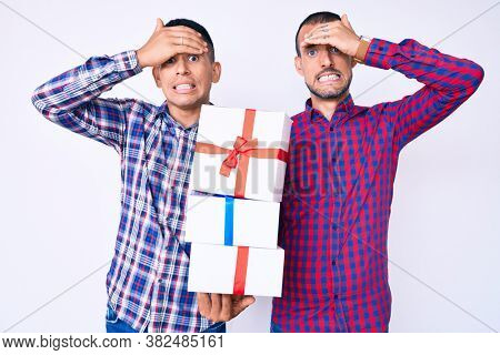 Young gay couple of two men holding gift stressed and frustrated with hand on head, surprised and angry face