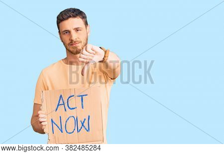 Handsome young man with bear holding act now banner with angry face, negative sign showing dislike with thumbs down, rejection concept