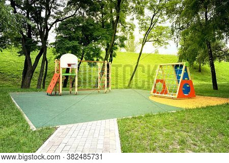 Colorful Playground On Yard In Park. Сhildren Playground Surrounded By Green Trees In Sunlight Morni