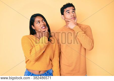 Beautiful latin young couple wearing casual clothes together thinking worried about a question, concerned and nervous with hand on chin