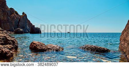 Summer Vibe. Virgin Nature Landscape. Nude Beach. Crystal Clean Ocean Water. Boat Floating On Horizo
