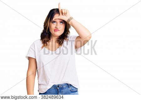 Young beautiful caucasian woman wearing casual white tshirt making fun of people with fingers on forehead doing loser gesture mocking and insulting.
