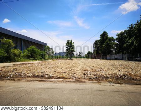 Land For Sale Concept. Landscape Of Empty Land Plot For Development, And Beautiful Blue Sky.
