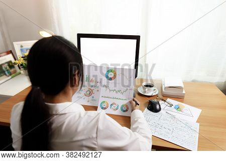 Rear View Of Businesswoman Working In Office With Computer Holding Chart Report Paper And Looking. B