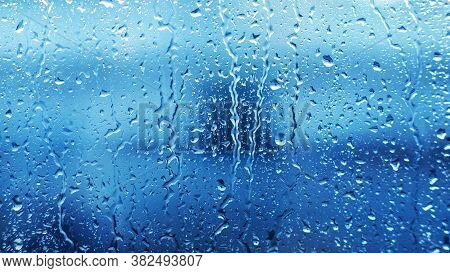 Drops Of Heavy Rainfall On The Clear Transparent Glass Of The Window In Cloudy Weather During The Da
