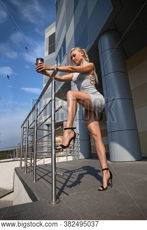 Beautiful Blonde Girl In Grey Dress With Perfect Legs And Shoes With High Heels Posing Outdoor At Th