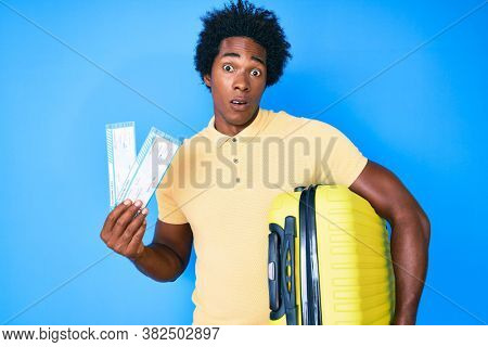 Handsome african american man with afro hair holding cabin suitcase and boarding tickets in shock face, looking skeptical and sarcastic, surprised with open mouth