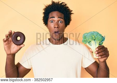 Handsome african american man with afro hair holding broccoli and chocolate donut in shock face, looking skeptical and sarcastic, surprised with open mouth