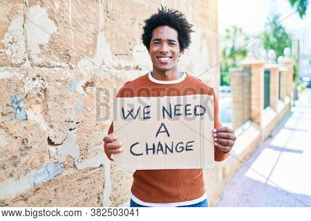 Young handsome african american man asking for change smiling happy. Standing with smile on face holding we need a change banner cardboard at town street.