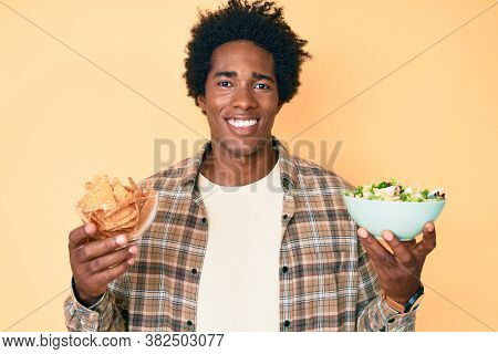 Handsome african american man with afro hair holding nachos and healthy salad smiling with a happy and cool smile on face. showing teeth.