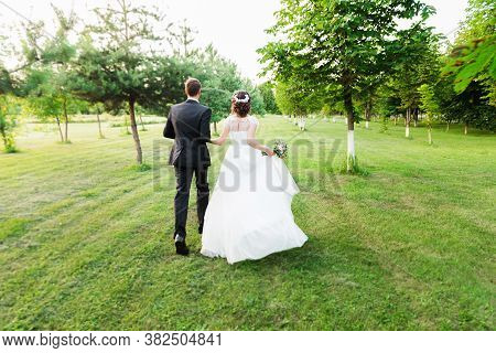Just Married Couple Running Away In A Green Summer Garden. Happy Bride And Groom Walking Running And