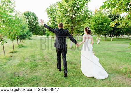 Just Married Couple Running Away Happily Waving Their Hands In A Green Summer Garden. Just Married L