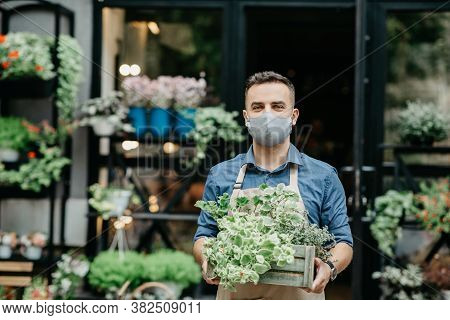 Small Business And Start Of Working Day. Man In Protective Mask Takes Out Box Of Plants Outside In F