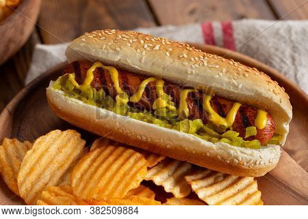 Grilled Hot Dog With Mustard And Relish On A Sesame Seed Bun And Potato Chips On A Wooden Plate