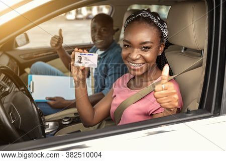 Happy African Girl With Driving License And Her Instructor Showing Thumb Up Inside Car, Woman Passed