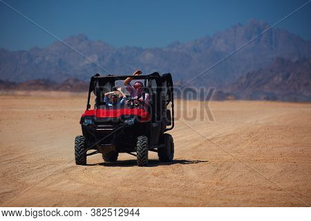 Excited Family Having A Safari Tour Through The Desert In Buggy Car. Thrill Adventures