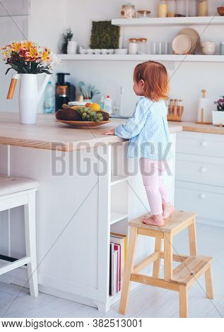 Curious Infant Baby Girl Trying To Reach Things On The Table In The Kitchen With The Help Of Step St