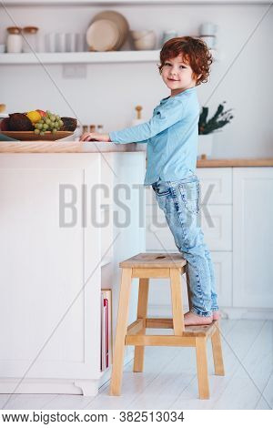 Cute Redhead Kid, Boy Standing On Step Stool In The Kitchen