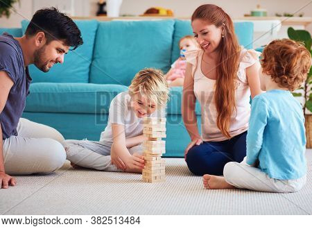 Cheerful Family Having Fun, Playing Wooden Block Tower Game Together On The Carpet At Home