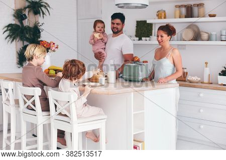 Happy Family With Three Kids Having Breakfast At Home In The Morning, Modern Kitchen Interior